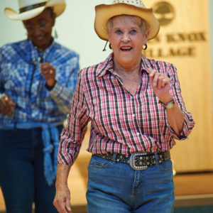 Seniors dressed in cowboy or southern living outfits practicing line dancing